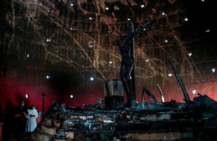"""A priest and a nun pray next to the image of """"Christ's Blood"""" after a fire burnt it at the Cathedral in Managua on July 31, 2020. Credit: Oswaldo RIVAS / POOL / AFP via Getty Images"""